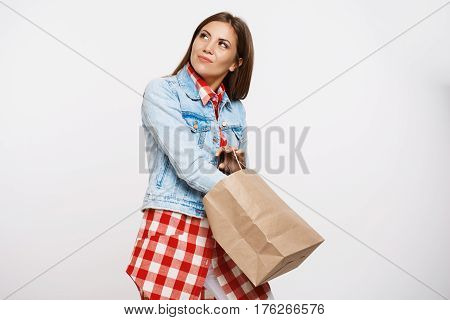 Fashionable woman in check dress searching for something lost in her handbag looking away