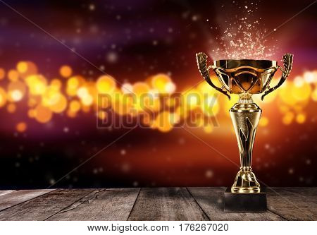 Champion golden trophy on wood table with blur spot lights on background. Copyspace for text, wide banner format. Concept of success and achievement.