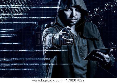 Internet crime concept. Dangerous hacker in hoodie shirt and dark digital background around stealing your data.