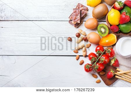 Selection of allergy food, orange citrus juice milk red tomato strawberry kiwi eggs chocolate nuts bread gluten on a rustic wooden table. Copy space background, top view flat lay overhead