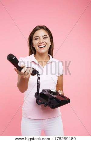 Smiling young woman in cool casual outfit makes phonecalls and holds receiver isolated on pink