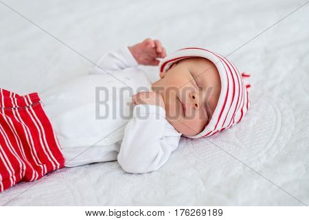 Sleeping newborn baby on back on white bed in a striped white and red cap and sliders. Close up