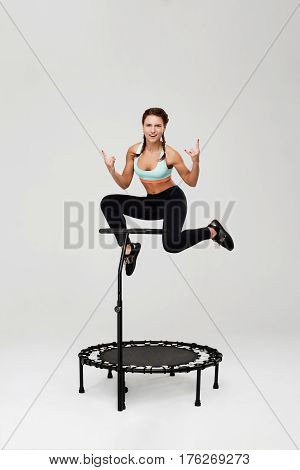 Young sporty woman training on rebounder and showig rock sign smiling and looking straight