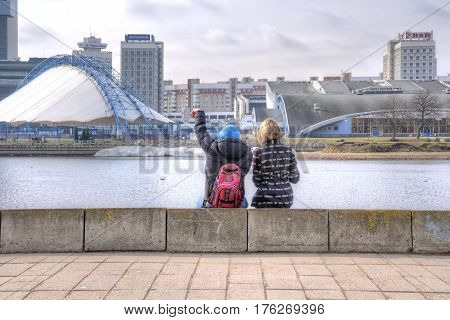 BELORUSSIA MINSK - March 11.2017: Fellow and girl sit on the parapet of the river Svislach