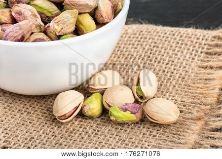 Pistachios unshelled in a bowl with scattered nuts on burlap