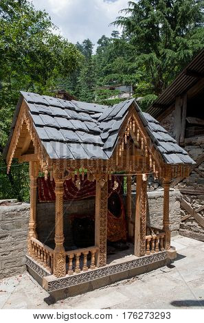 MANALI, INDIA. A small Shiva Temple decorated with wood-carved a swastika and iron tridents.  Naggar, district of Kullu in Himachal Pradesh, India.