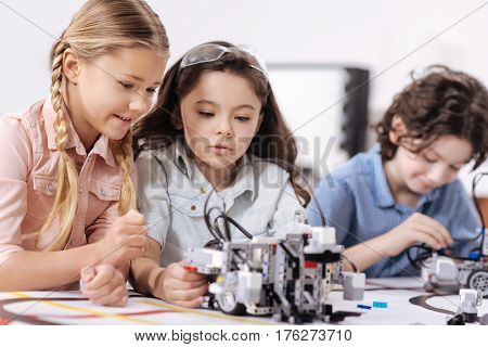 Discussing science. Involved pleasant charming children sitting at school and enjoying science class while expressing joy and having conversation
