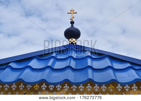 A small blue dome with a cross on the blue roof of the chapel against the blue sky.