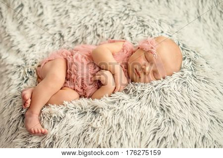 Portrait of a sleeping newborn girl a few days old. Newborn girl sleep in a pink tank tops and handmade bandage on her head on a fur rug. Ideas for newborn photo shoot
