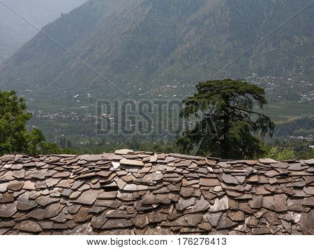 MANALI, INDIA. At home on the slopes of the Himalayas. Traditional roofs of flat stones. Naggar, district of Kullu in Himachal Pradesh, India.