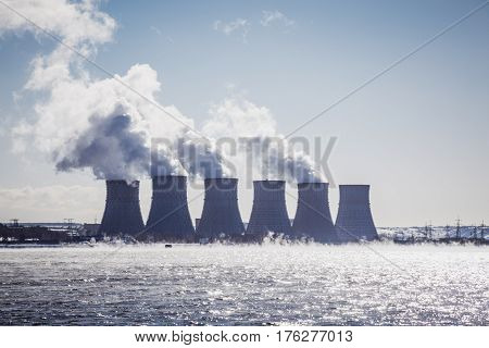 Cooling towers of a Nuclear Power Plant or NPP with thick smoke on blue sky background in sunny day. Copy space for text