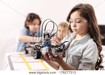 Applying my knowledge. Involved skilled smart girl standing at school and holding robot while colleagues working on the project