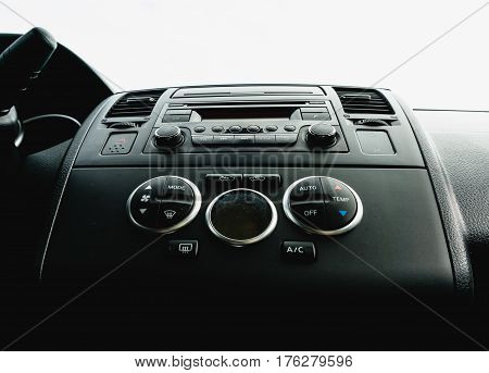 Interior view of vehicle. Modern technology car dashboard close up. Climate control and car audio panel.