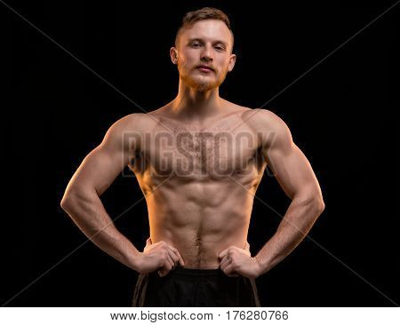 Young blond man with muscular torso on black background