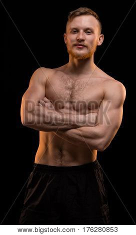Smiling muscular man with arms crossed on black background