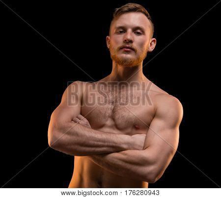 Muscular man with arms crossed on black background