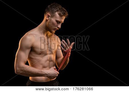 Bearded fighter man with boxing bandages on black background