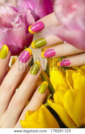Yellow green French manicure with pink nail Polish and tulips closeup.Nail art.