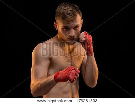 Fighter with boxing bandages on black background