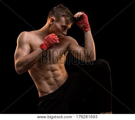 Muscular man during boxing training on black background