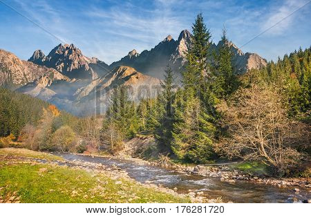 beautiful autumn landscape. composite image of High Tatra ridge. rocky shore of the river in fog that flows near the forest at the foot of the mountain.