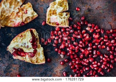 Pomegranate Fruit And Seeds Over Black Rustic Surface.