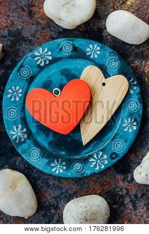 Two Hearts On Blue Plate Over Rustic Background