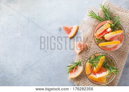 Healthcare, fitness, healthy nutrition concept. Fresh cool grapefruit rosemary infused water, cocktail, detox drink, lemonade for spring summer days. Top view overhead flat lay, copy space background