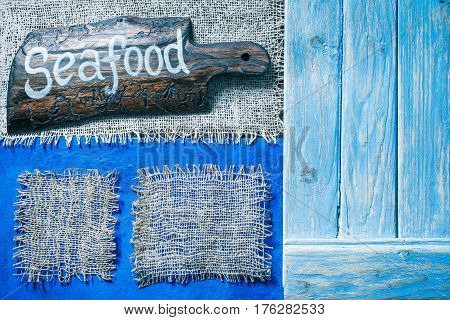 Burlap frames on blue painted wood boards. Dark wooden cutting board with text 'Seafood' as title bar. Structured shabby style background for natural food and drink industry