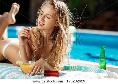Young beautiful blonde girl in swimwear drinking cocktail,  sunbathing, lying near swimming pool. Copy space.