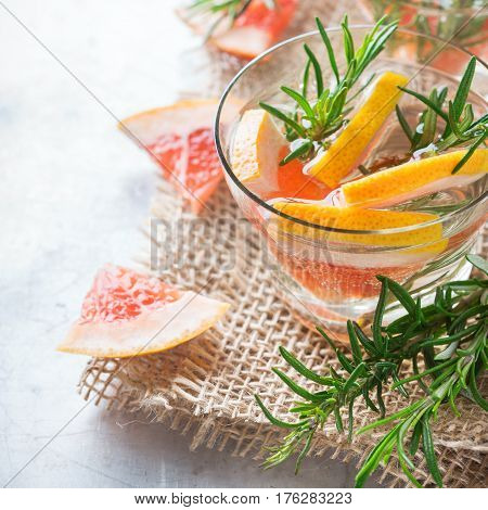 Healthcare, fitness, healthy nutrition concept. Fresh cool grapefruit rosemary infused water, cocktail, detox drink, lemonade for spring summer days on a rustic table