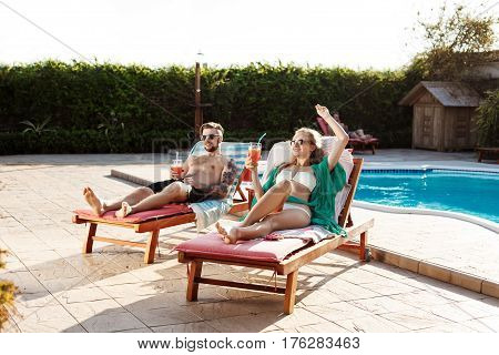 Young beautiful friends smiling, drinking cocktails, lying on chaises near swimming pool. Copy space.