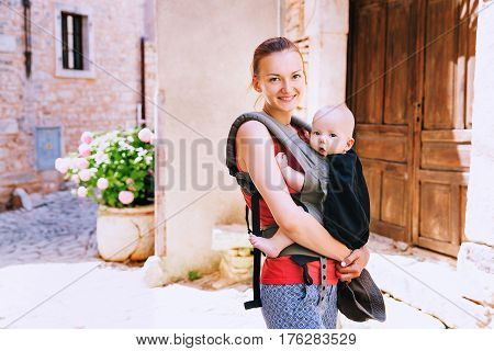 Beautiful young mother with baby child in carrier in the old town of Pula Croatia. Travel family of tourists on the background of the European street. Active travel family vacation