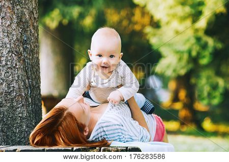 Baby and mother on nature in the park at summer day. Happy family walking outdoors