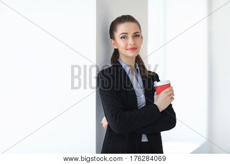 Portrait Of Young Beautiful Business Woman With Cup Of Coffee In The Office