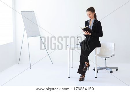 Portrait Of Beautiful Business Woman Reading Notebook In The Office