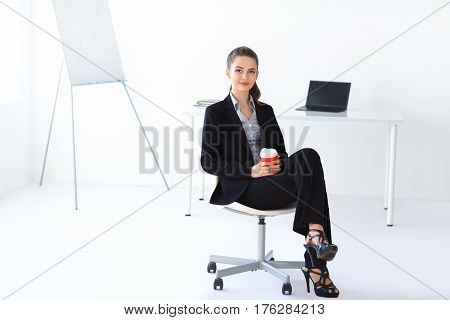 Beautiful Business Woman Sitting On Chair With Cup Of Coffee In The Office