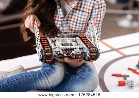 Enjoying tech class. Involved talented little girl sitting in the robotics laboratory and holding details of cyber robot while having tech class