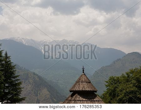 MANALI, INDIA. The wooden roof of the Tripura Sundari Temple on the backdrop of Himalayas on a cloudy day. Naggar, district Kullu in Himachal Pradesh, India.