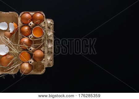 Fresh chicken eggs background. Brown eggs in craft carton pack on hay on black with copy space. Top view. Natural healthy food and organic farming concept.