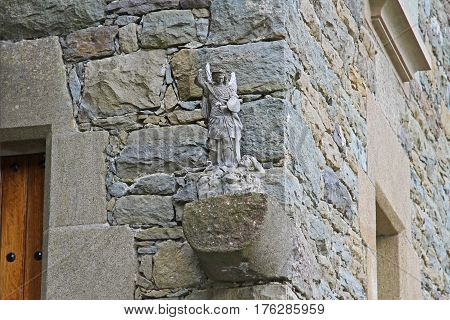 Sculpture of angel defeating the enemy on the background of a stone building in Rupit (Catalonia Spain)