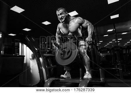 Athlete Muscular Bodybuilder In The Gym Training Biceps With Bar