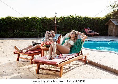 Young beautiful friends in swimwear sunbathing, lying on chaises near swimming pool. Copy space.