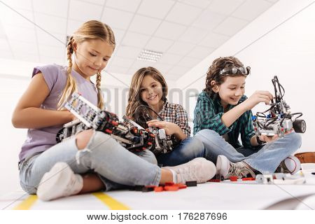 Working in group. Charming cheerful inspired children sitting in the science studio and using gadgets and devices while expressing positivity