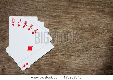 Five card of red diamond royal straight flush on wooden background