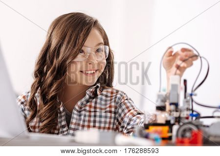 Enjoying my hobby. Smiling smart gifted kid sitting in the science studio and using devices while studying and expressing happiness