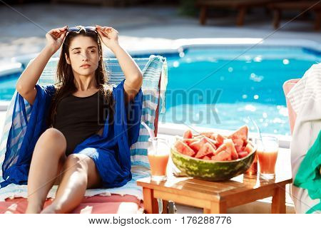 Beautiful brunette girl sunbathing, lying on chaise near swimming pool. Copy space.