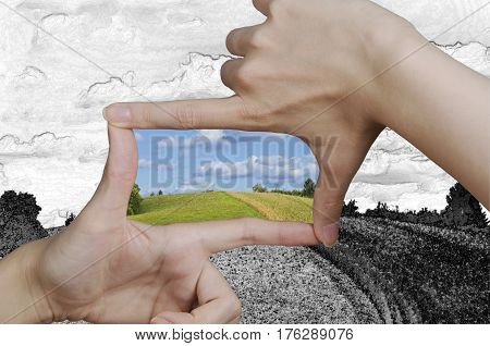 hands creating a square turning a drawing of a clean landscape into reality