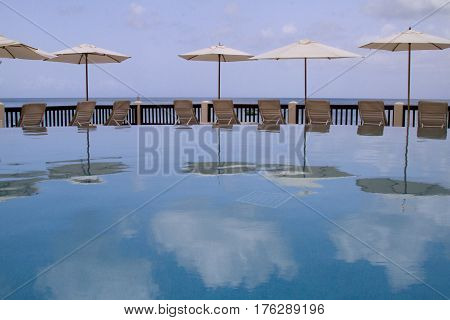 Reflections in infinity pool with sun shades