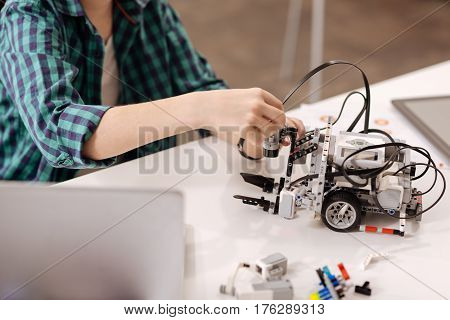 Creating cybernetic robots. Capable smart young boy sitting at school and using digital gadgets while studying and expressing joy